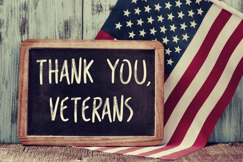 A chalkboard sign with Thank you veterans in front of an American Flag