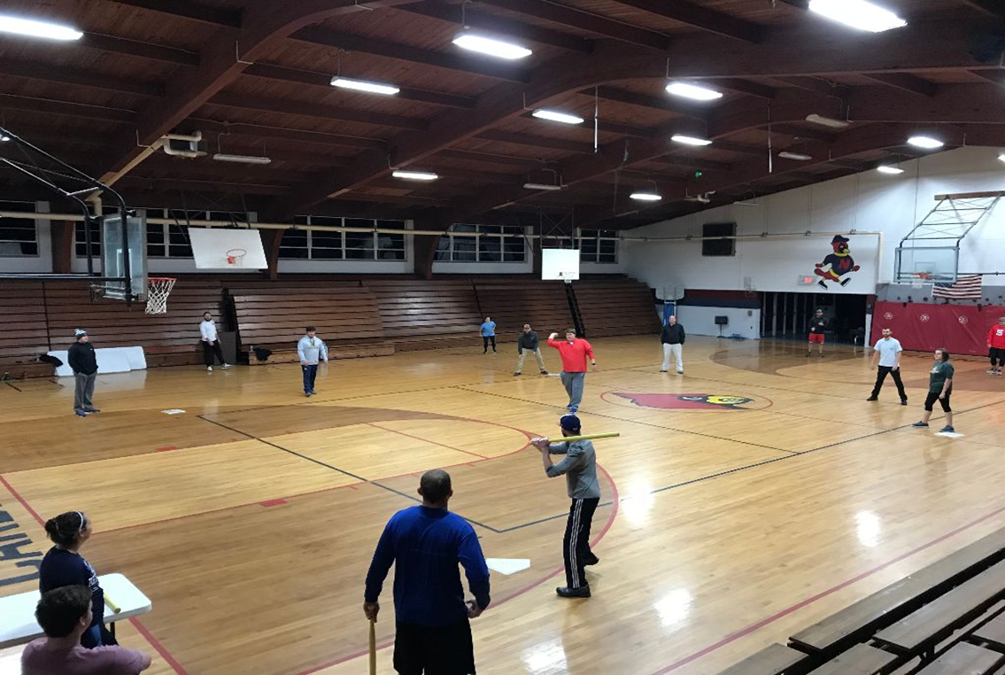 adults playing baseball inside a gym
