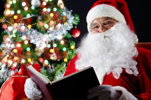 Santa sitting in chair reading a book by a tree